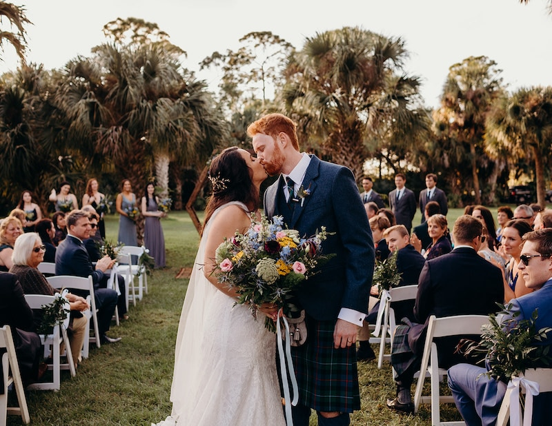 bride and groom kissing after their outdoor florida wedding ceremony