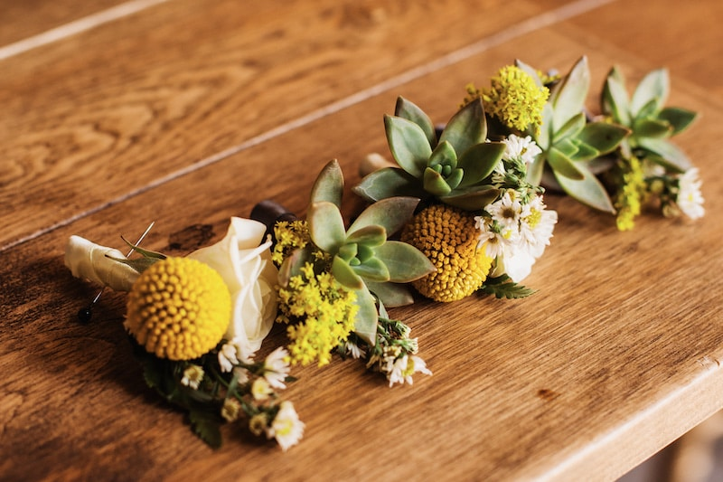 boutonnieres sitting on wooden table before being pinned to groom and his groomsmen