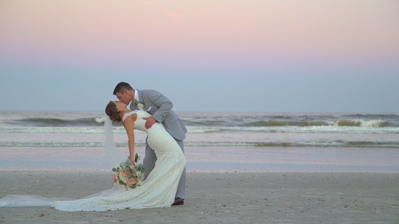 bride and groom kissing on a beach at twilight