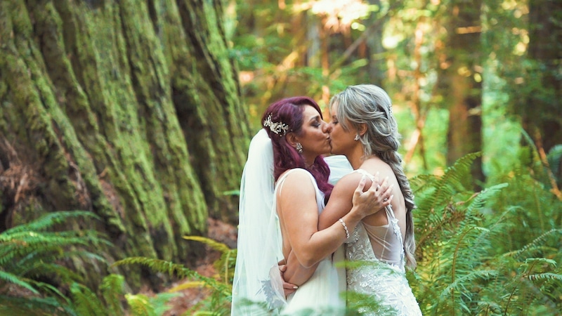 brides kissing while standing in a forest under a large tree