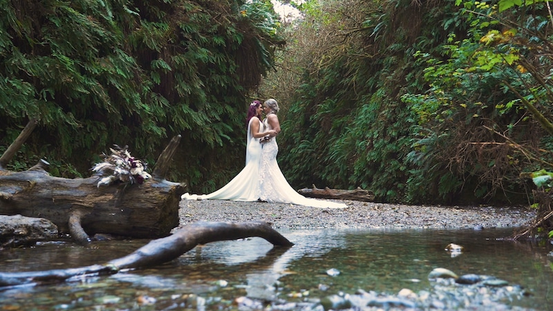 brides kissing while standing in a forest next to a shallow creek