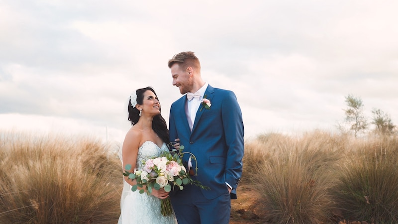bride and groom smiling at each other while standing next to dunes at the beach
