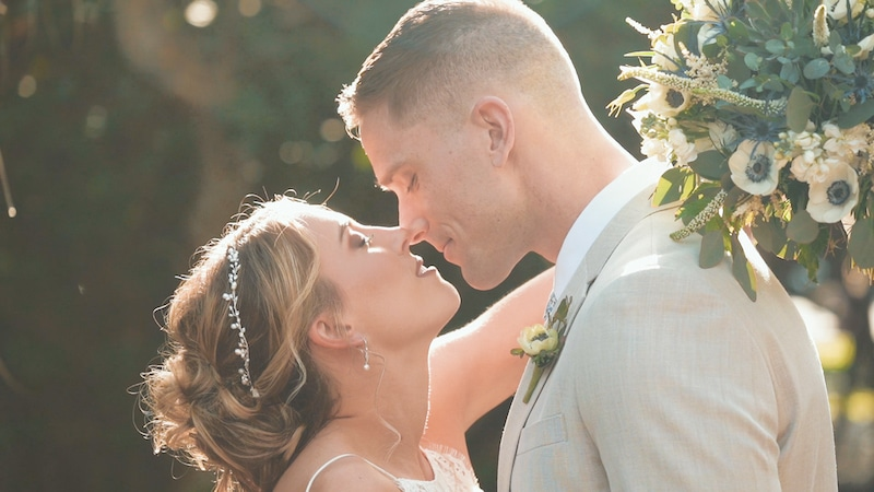 bride and groom kissing while standing outside in a garden