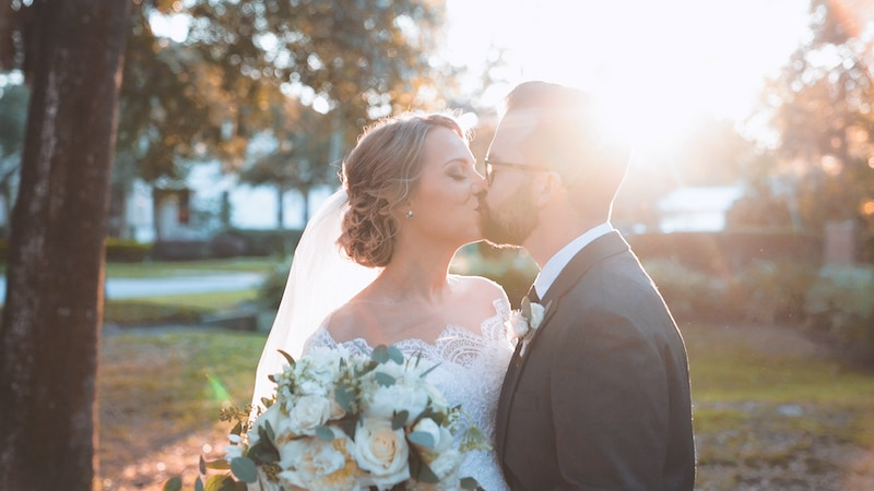 bride and groom kissing as the sun sets behind them