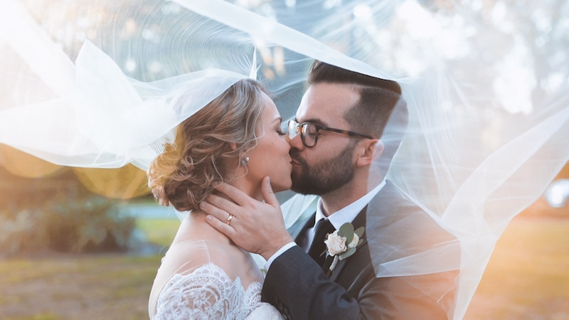 bride and groom kissing while the brides veil swirls around them