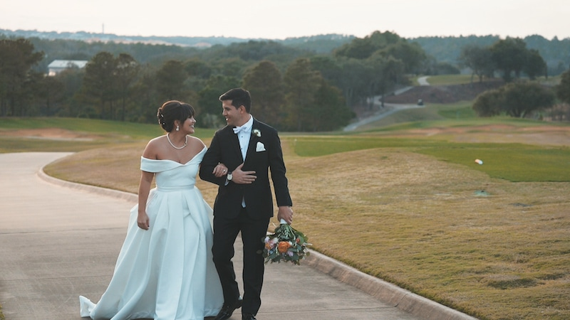 bride and groom walking arm in arm along a golf cart path