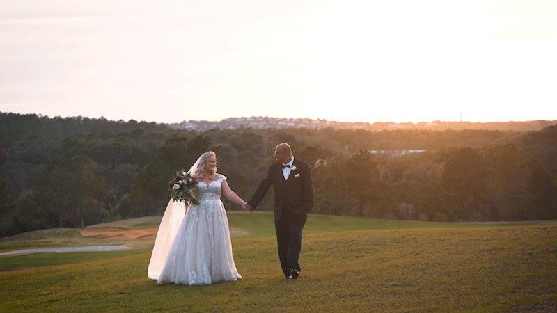 bride and groom standing on a golf course as the sun sets in the hills behind them