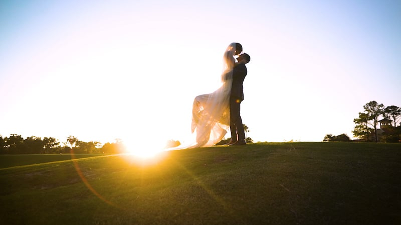 groom lifting his bride while standing on a golf course with the sun setting behind them
