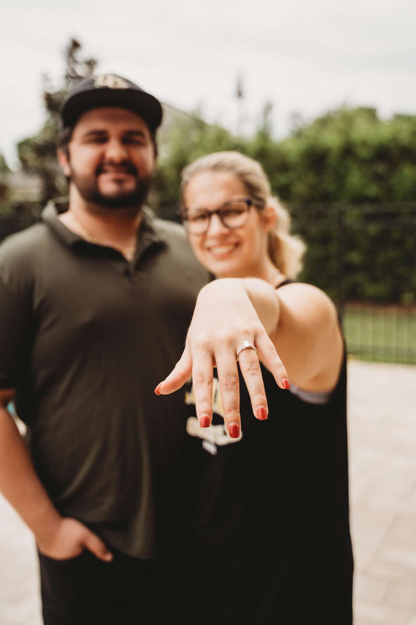newly engaged couple standing and bride showing off her new engagement ring