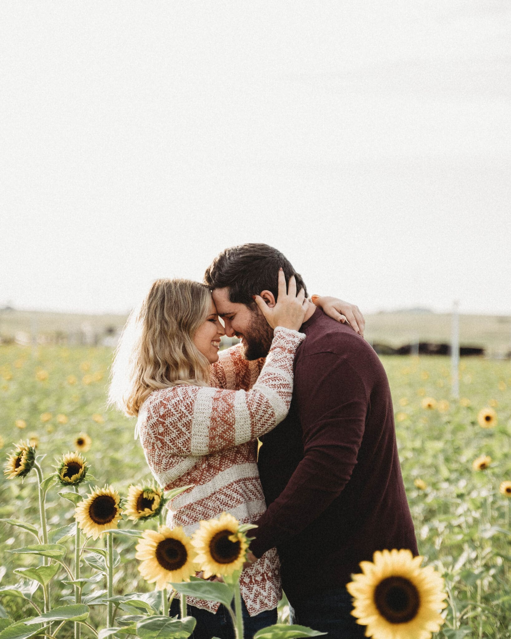 newly engaged couple standing in a sunflower field holding each other