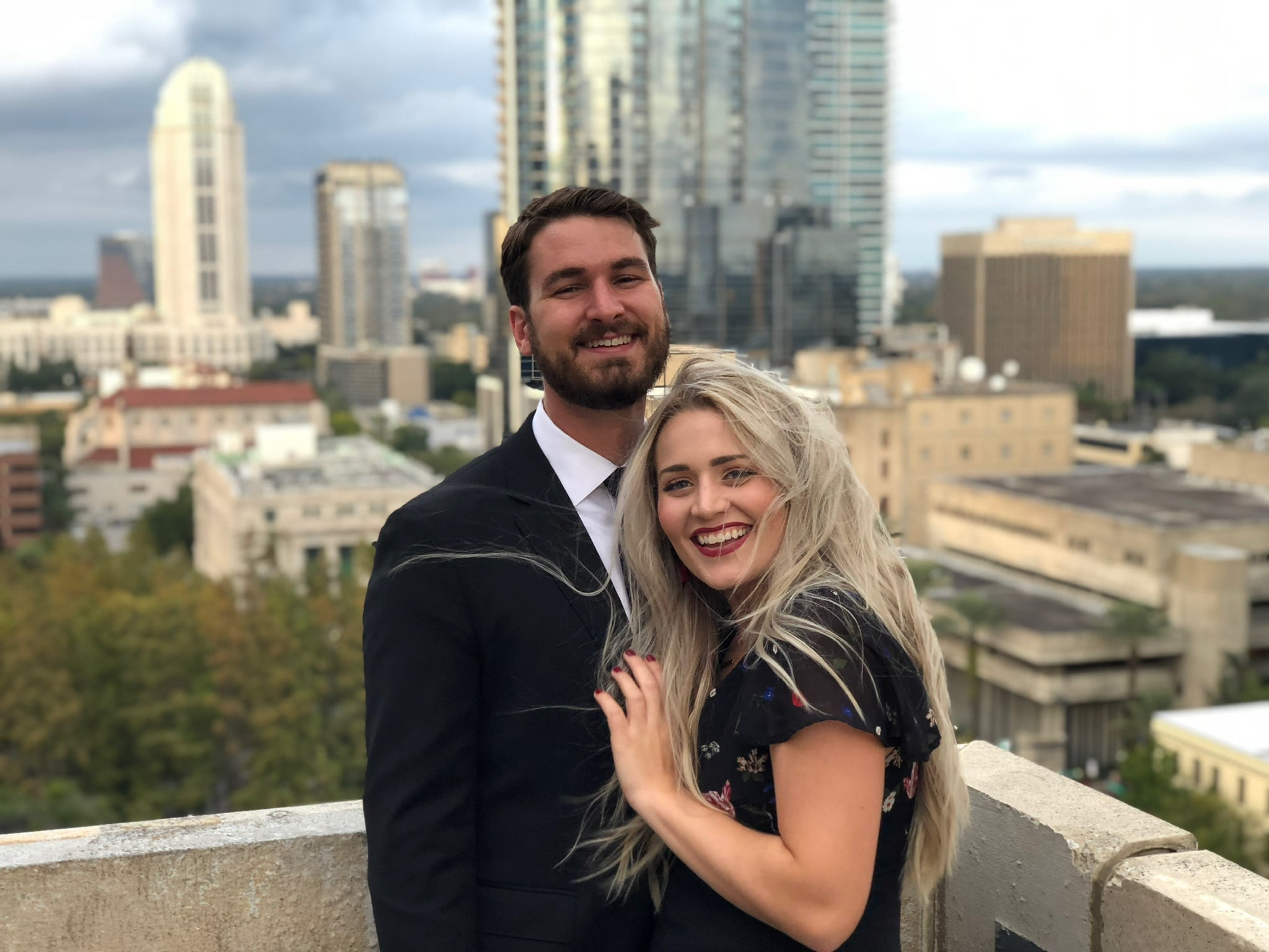 blonde haired woman stand against chest of man both dressed formally and smiling for a picture while on a rooftop downtown and building behind them