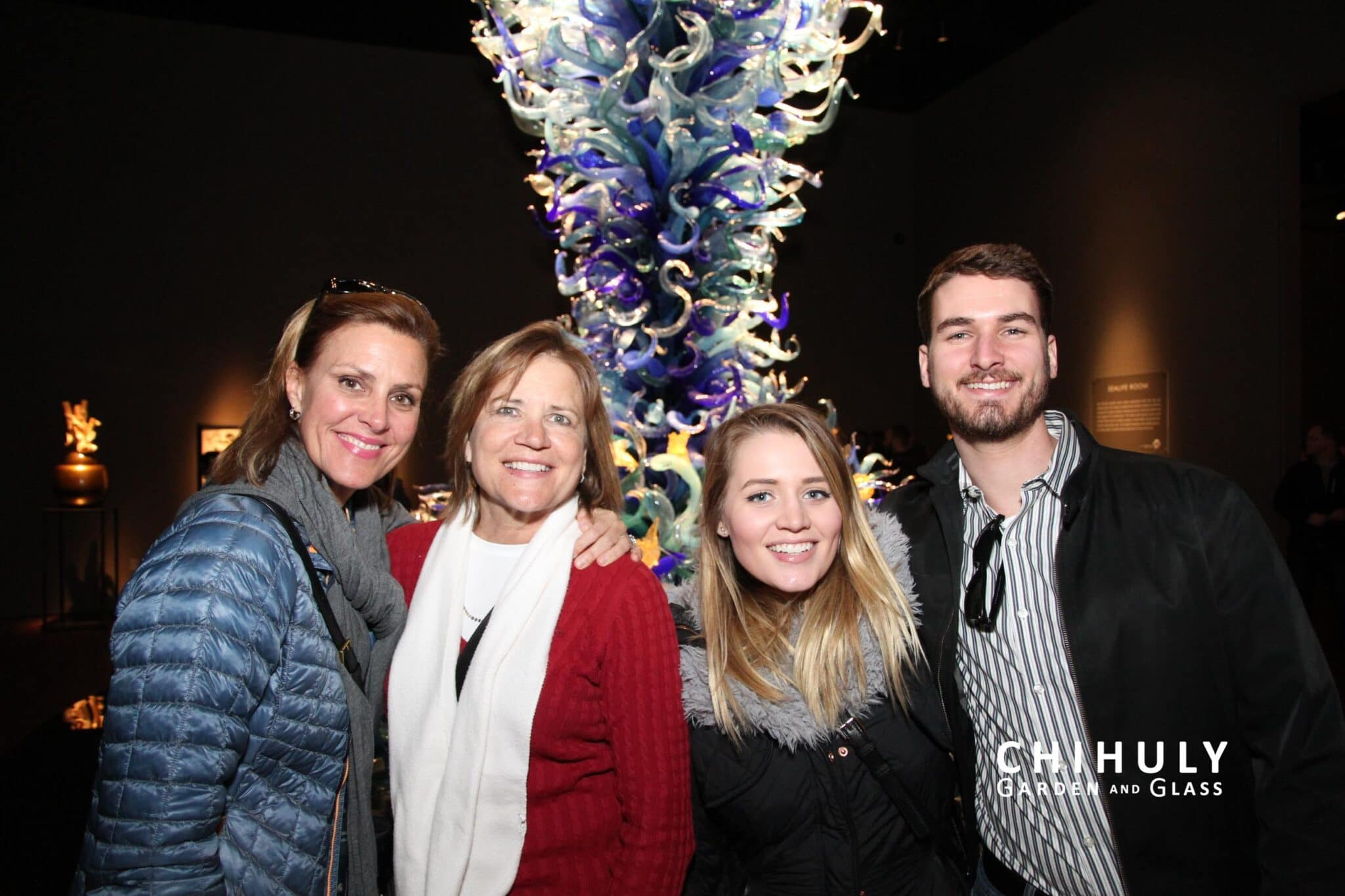 picture of two older woman and one younger woman with younger man standing in front of chihuly glass piece of artwork at the chihuly museum