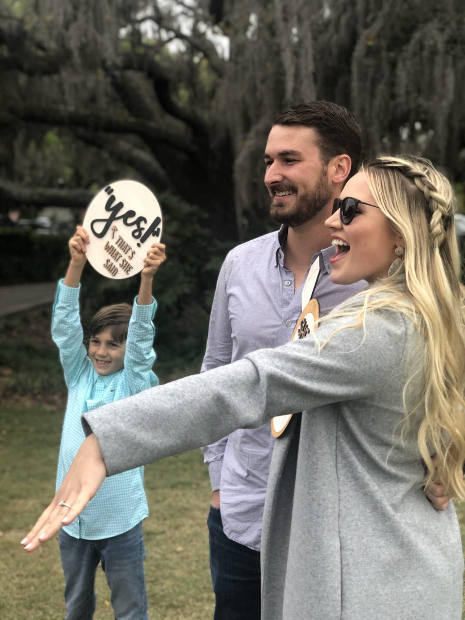 "woman wearing sunglasses smiles big and holds out hand with new engagement ring while man stands next to her and a child next to them holding a sign that says ""yes?"""