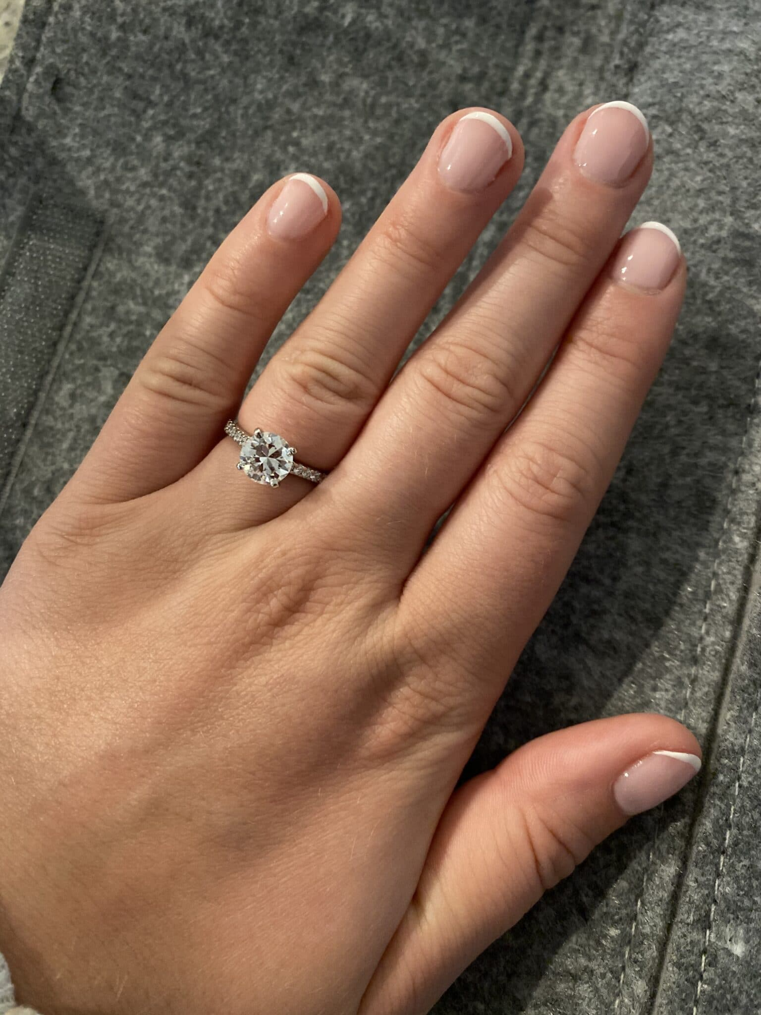 close up image of an engagement ring on hand on woman with french tip painted fingernails
