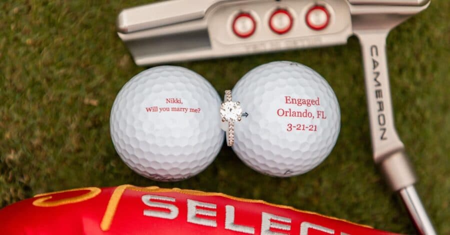 two custom golf course marriage proposal golf balls with will you marry my on them and an engagement ring in between with a golf club