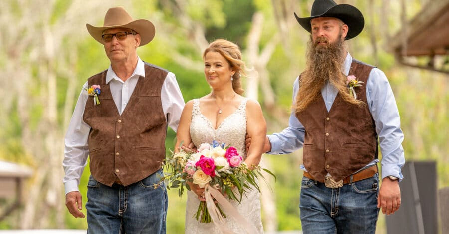 bride wearing sleeveless wedding dress holds bouquet in front of her with bright pink flowers while two men on either side of her walk her down the aisle on wedding day