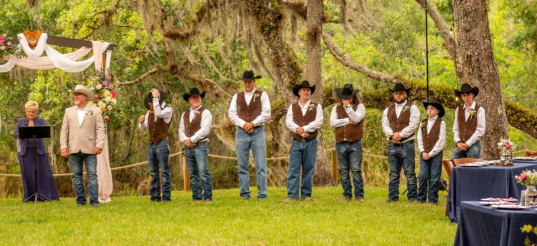 groom and eight groomsmen stand at the altar on wedding day outside with officiant