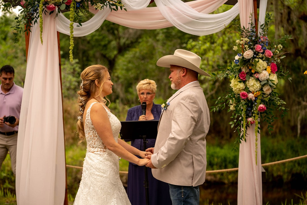 bride and groom stand facing each other holding hands at altar with officiant and arch behind them with drapery and flowers