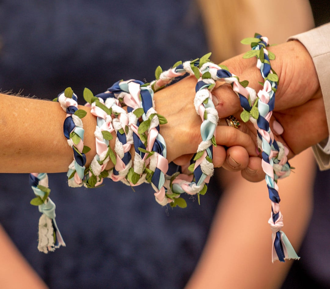 close up of man and woman holding hands with braided rope tied around them