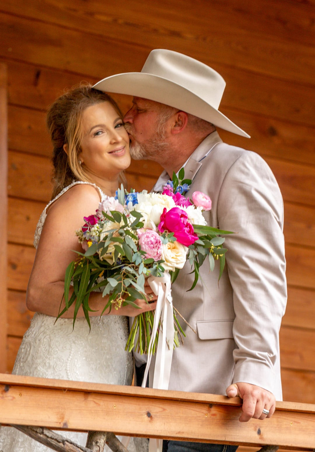 bride looks at camera smiling while holding bouquet in front of her and groom stands next to her holding the railing in front of them and kissing her on the cheek