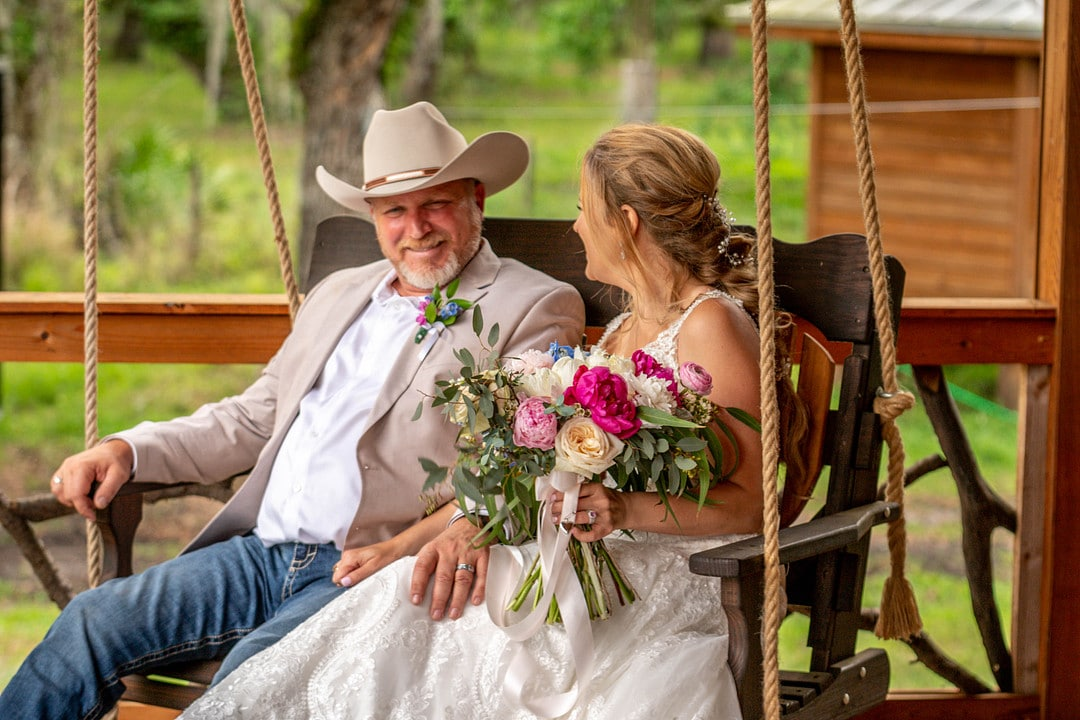 husband and wife sit together on wooden porch swing on wedding day while groom looks at camera and bride looks at him