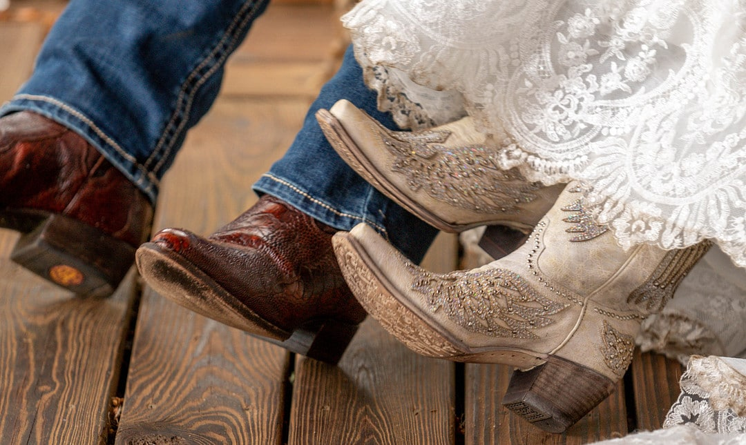 close up of couples brown and white cowboy boots on wedding day