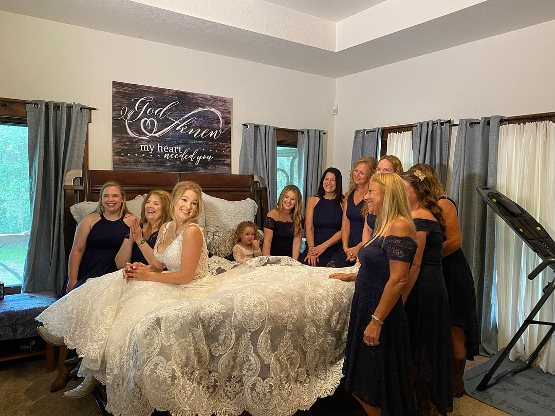 bride sits on bed with lace wedding dress spread out on the bed around her and all of her bridesmaids standing around the bed looking at her