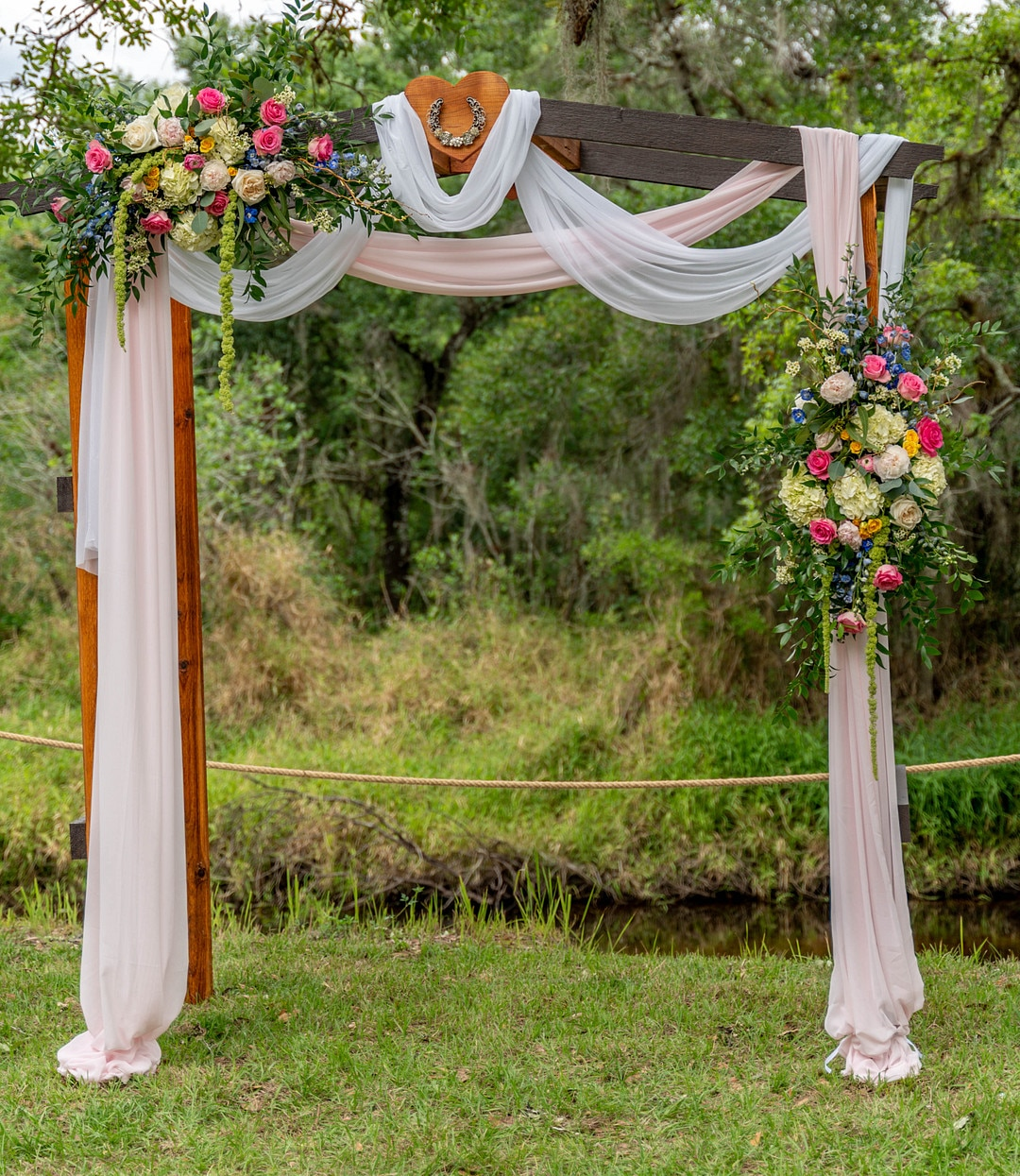 square wooden ceremony arch outisde with light pink and white drapery around it and two large flower arrangements hooked to it