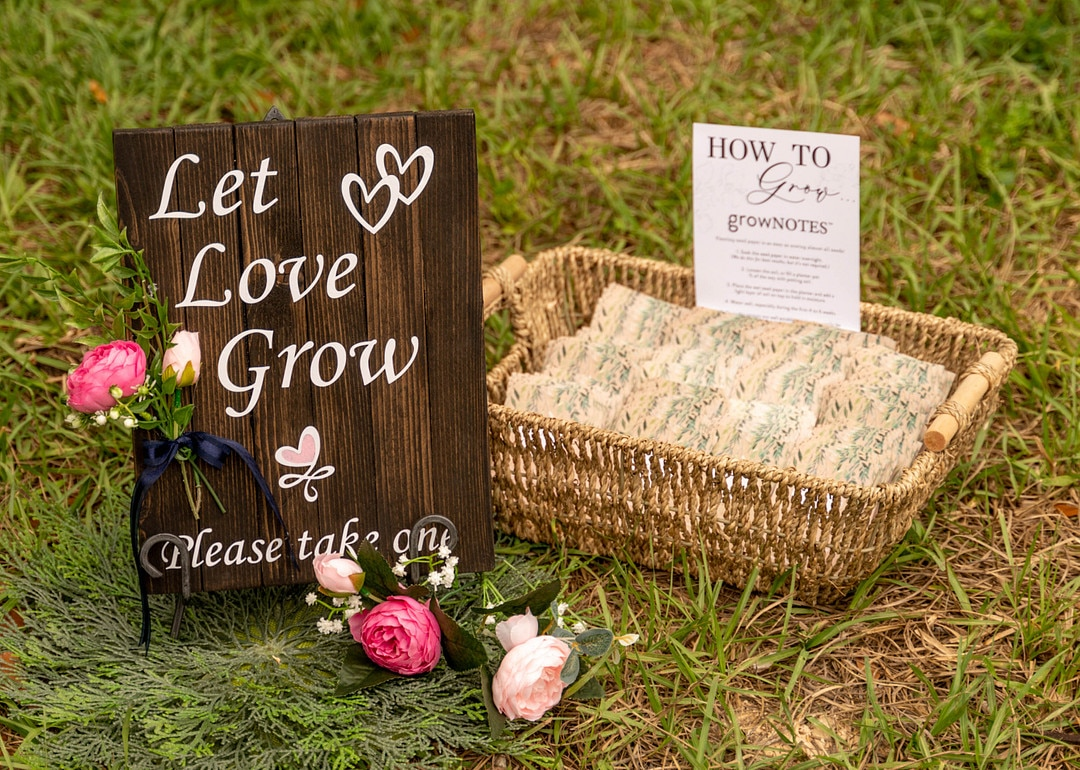 wicker basket with handles sits on the grass outside with wedding day favors inside and wooden sign next to it reading let love grow please take one