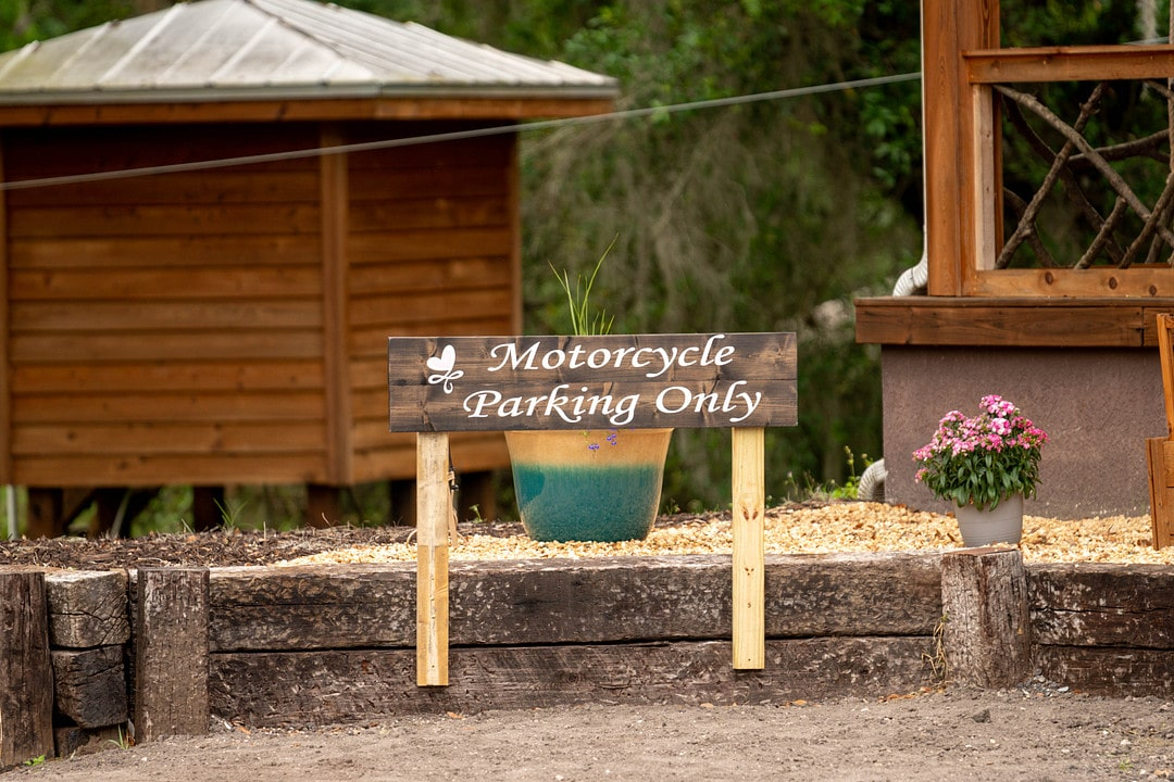 wooden sign outside of cabin with motorcycle parking only written on it and a small wooden structure built behind it