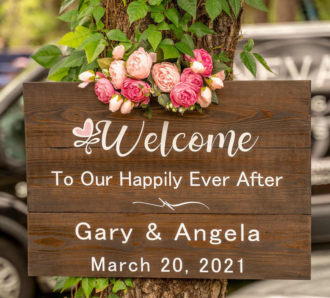 wooden wedding day welcome sign for gary & angela with white writing and pink peony arrangement secured to the top of the sign