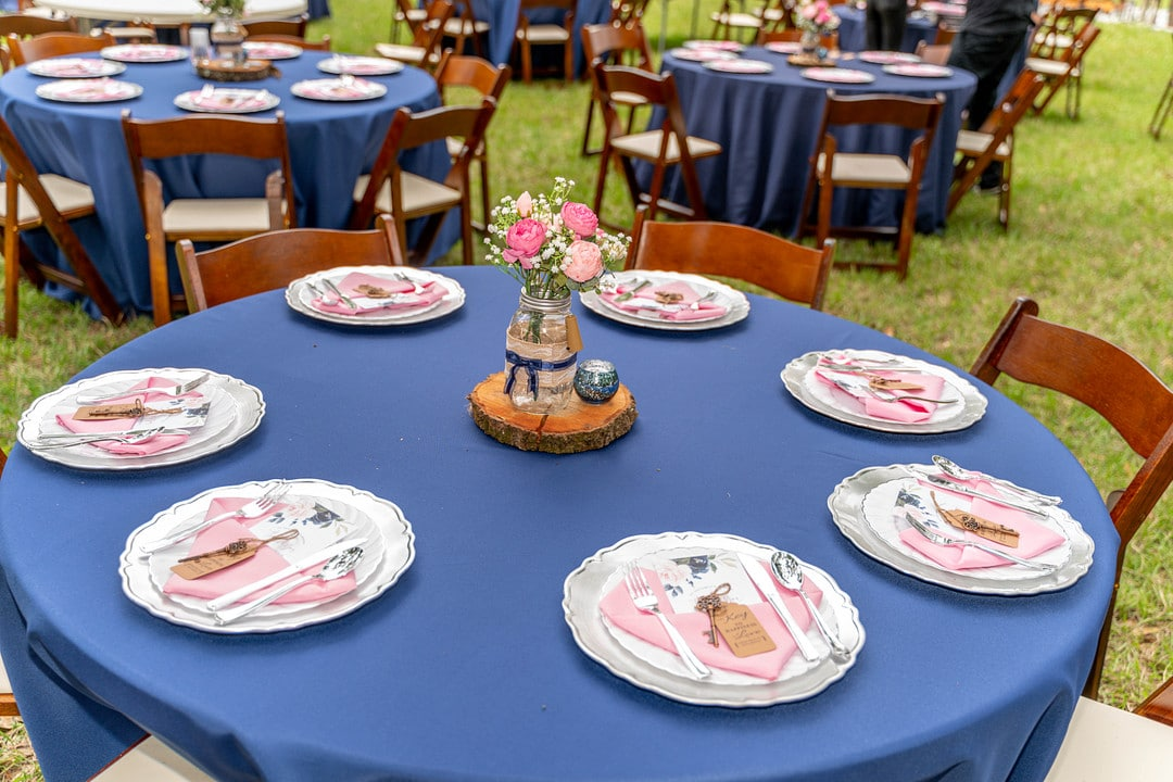 wedding reception tables setup with navy blue linen and wooden folding chairs with chargers and other favors at each place setting and wood slices and mason jars as centerpieces