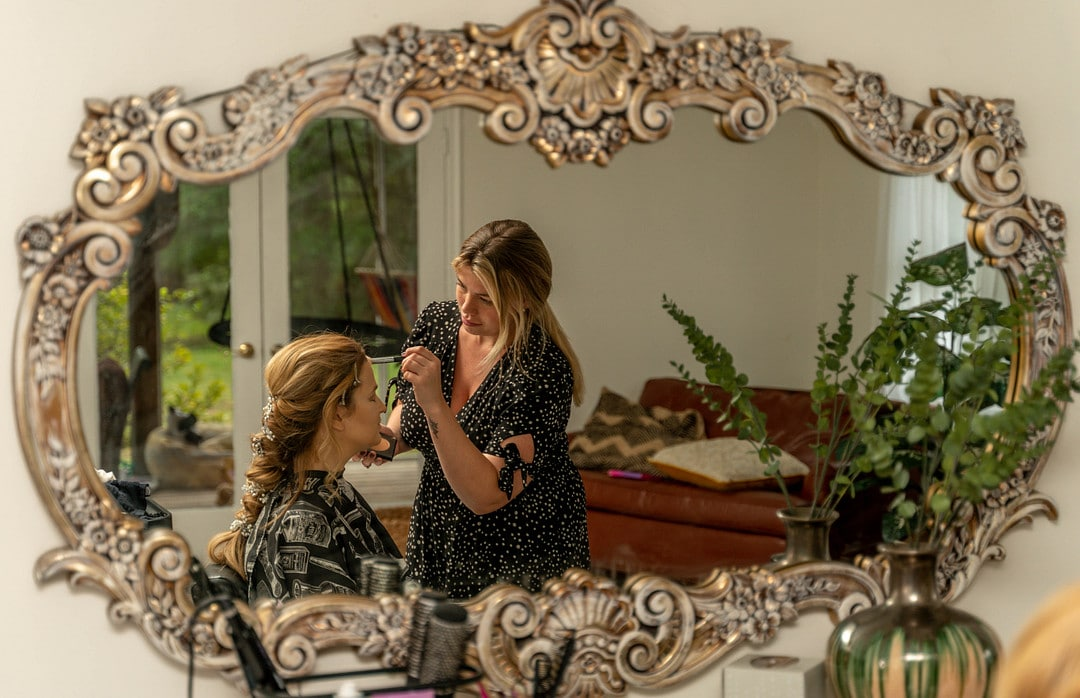 mirror picture of woman with braided hair sitting as makeup artist applies makeup