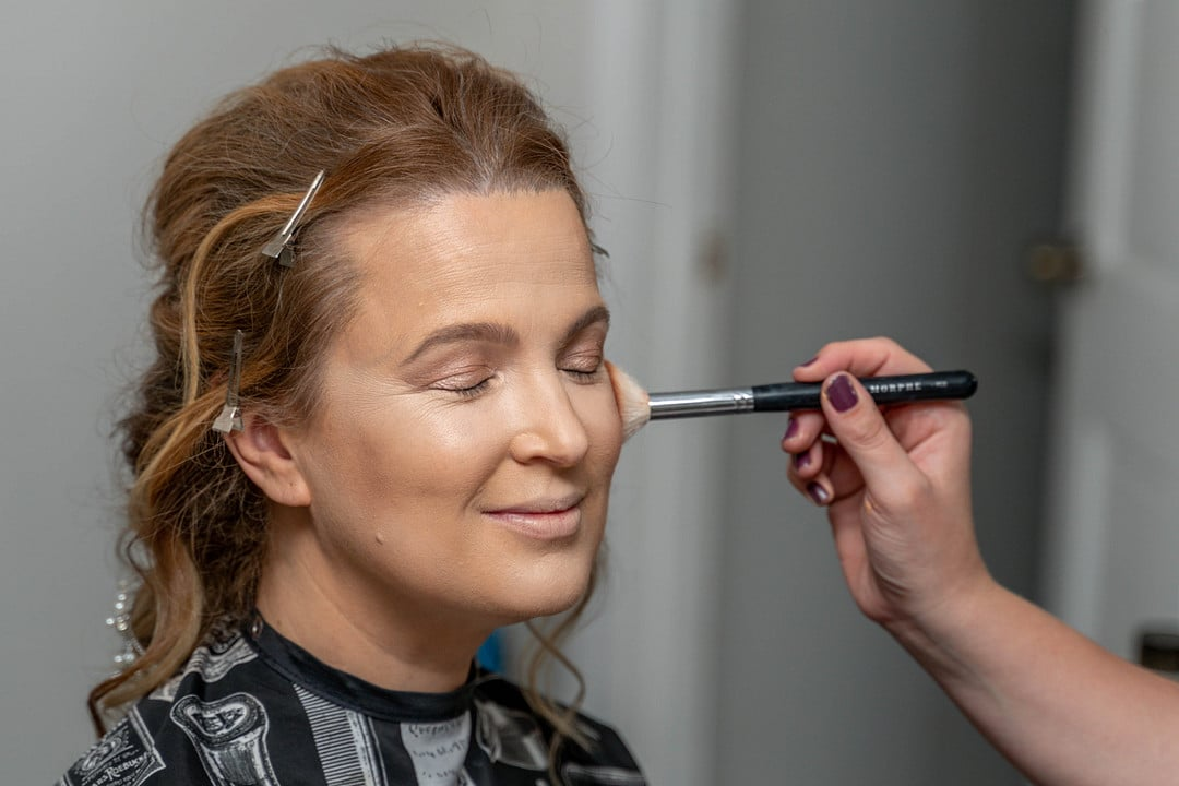 woman sits smiling with eyes closed and hair clipped back from face while another hand holds brush and applies makeup to her face with it