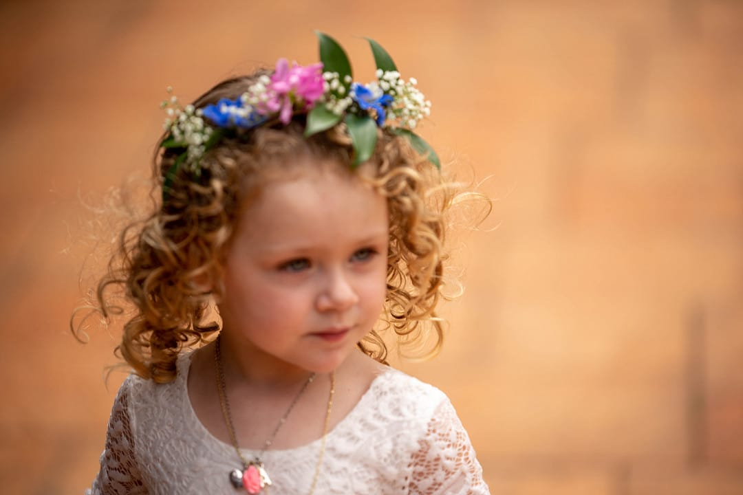 little girl with short curly hair wearing lacey white top and flower crown looking off to the side
