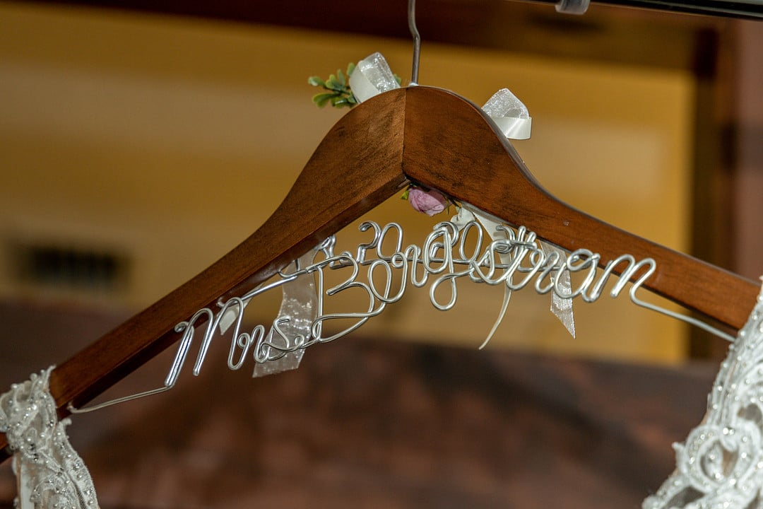 close up image of wooden hanger with wire underneath it reading mrs. bergstrom with wedding dress on hanger