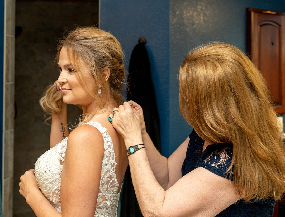 woman with red hair stands behind bride clipping necklace onto bride holding her braided hair out of the way looking off to the side