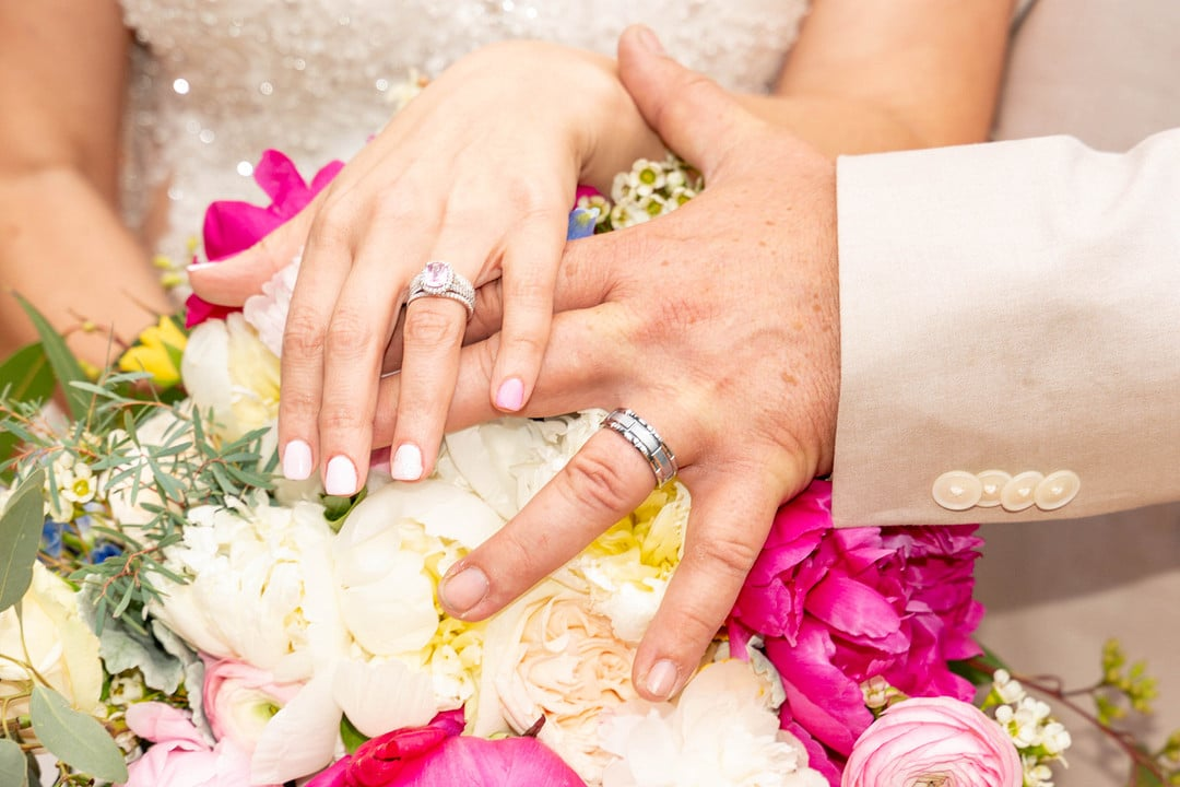 close up image of bride and grooms hands on top of bridal bouquet together showing of their wedding rings