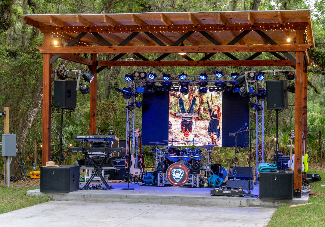 outside covered paved area set up with stage for a band with lights and speakers