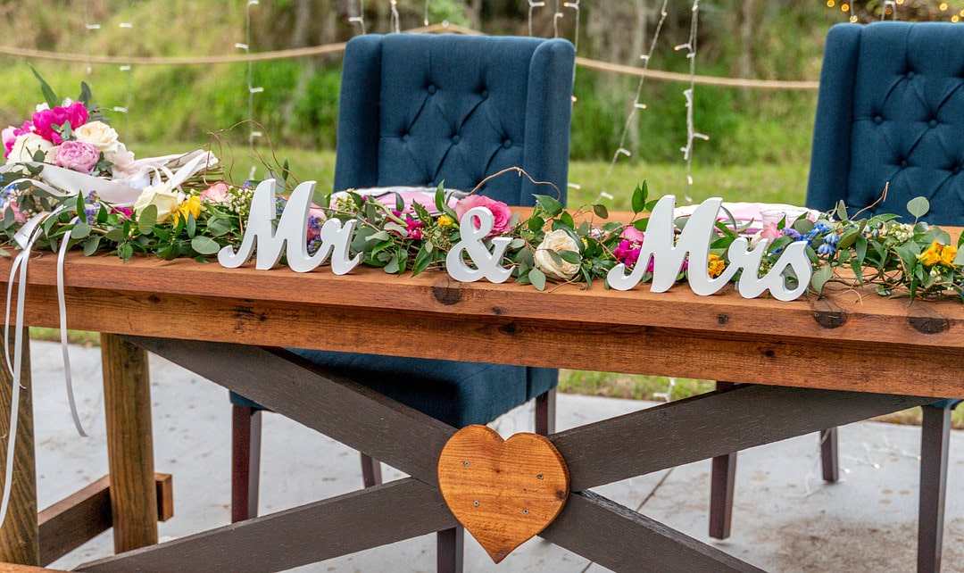 wedding day sweetheart table with wooden heat attached to the front and silver mr and mrs signs with garland floral behind them and navy blue fabric chairs