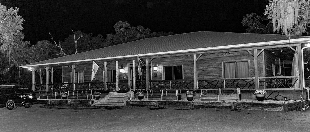 black and white image at night of large cabin surrounded by trees