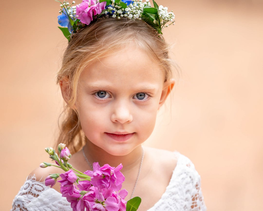 little girl wearing lacey white top with pink snap dragon in front of her looking at camera with hair pulled back and flower crown in her hair