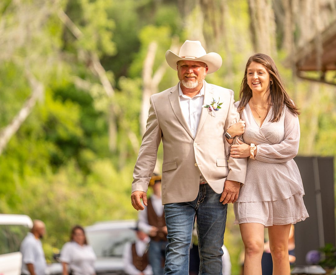 man wearing a beige blazer with blue jeans and a cowboy hat walks down aisle on wedding day with woman holding his arm wearing a light colored dress