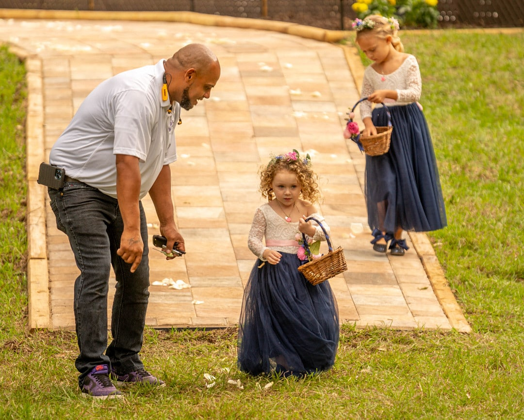 man stands beside little girl wearing a white and navy blue dress with flower crown throwing flower petals from basket down the aisle with another girl behind them on a brick paved path wearing the same thing also throwing flower petals