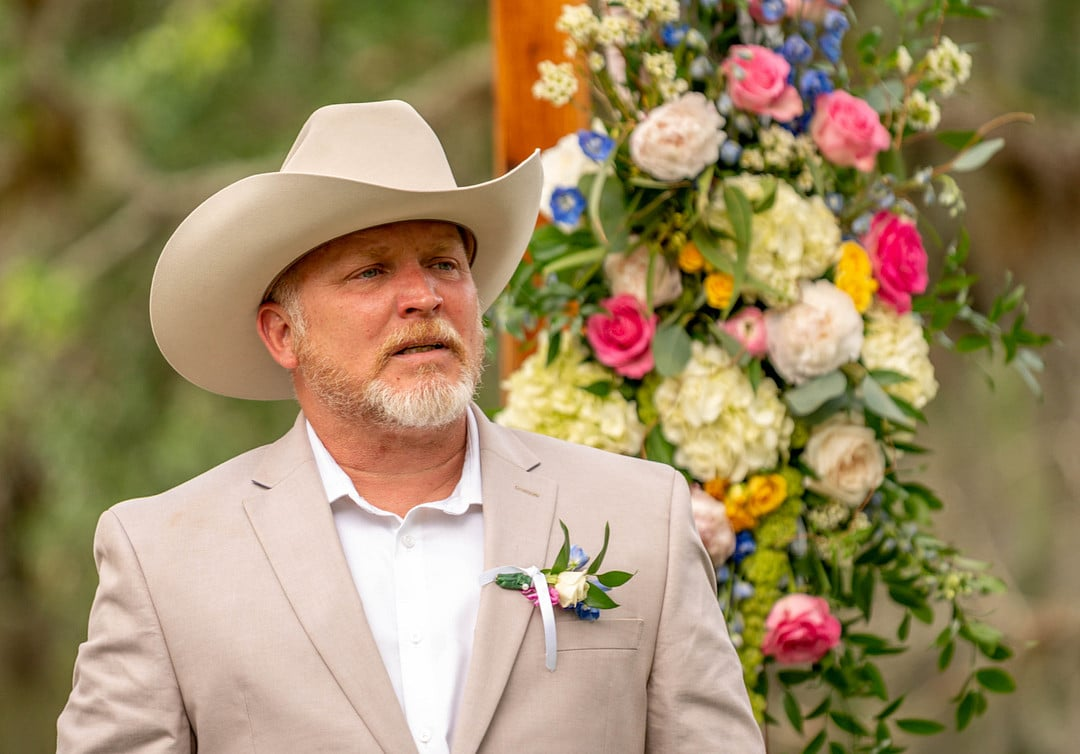 close up image of groom on wedding day wearing beige blazer and cowboy hat with face full of emotion with a flower arrangement behind him