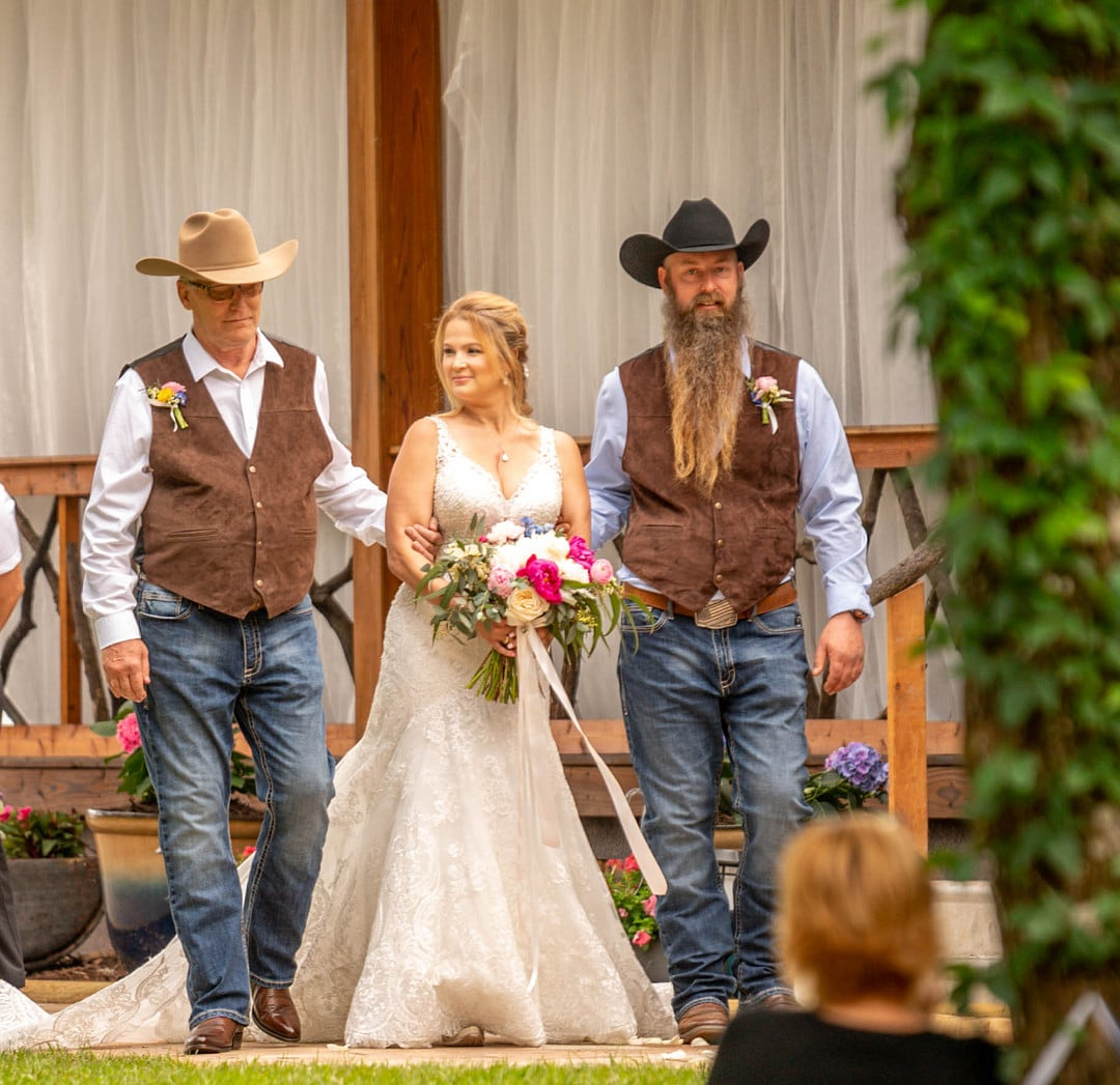bride holding big flower bouquet walks down the aisle with two men on each side of her wearing jeans button down shirts brown vests and cowboy hats