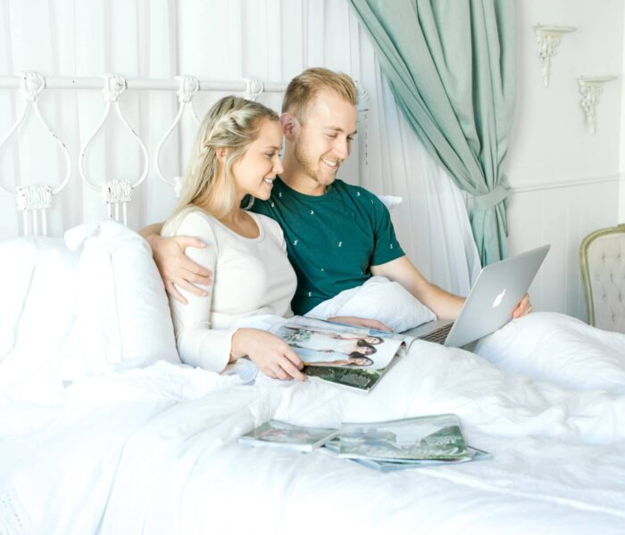 engaged couple lying in bed reading wedding magazines and looking at the Wedding Venue Map website on their laptop