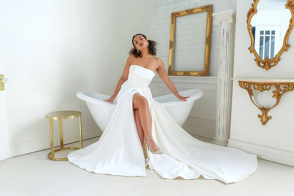 bride sitting on the edge of a stand alone tub in a white bathroom