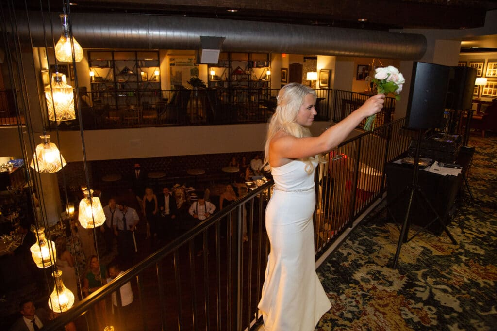 bride standing on balcony on second floor of reception area getting ready to through bouquet down to the guests