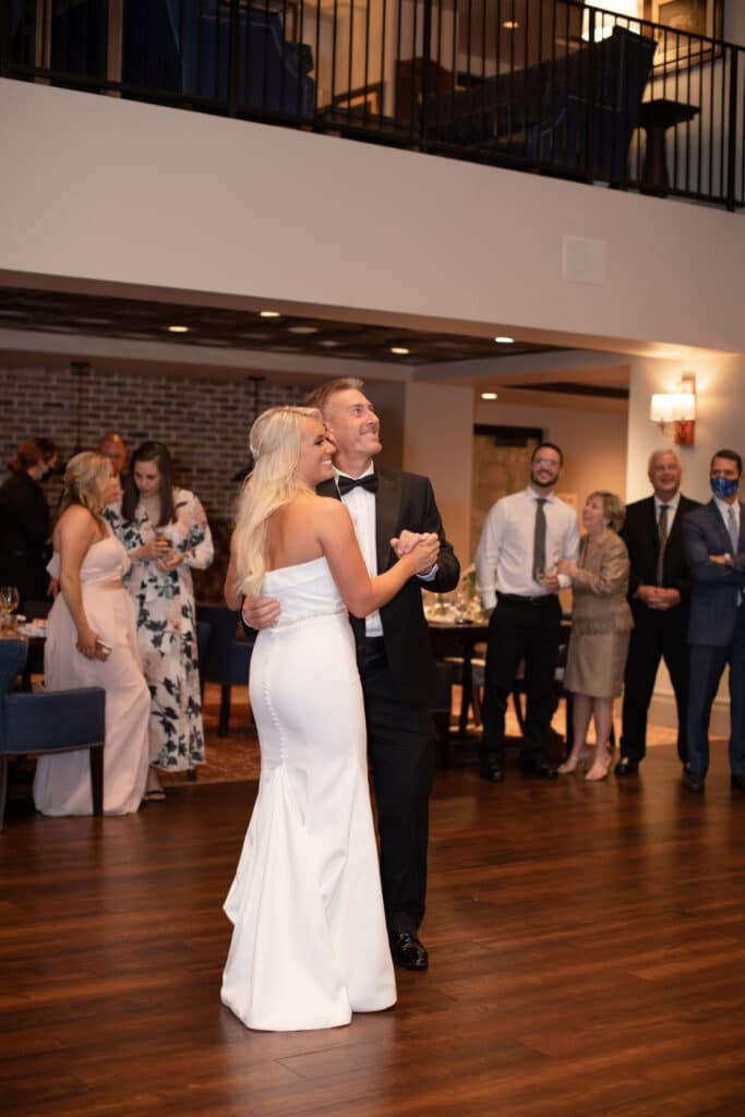 bride and groom having their first dance on wood dance floor and looking up toward second level balcony
